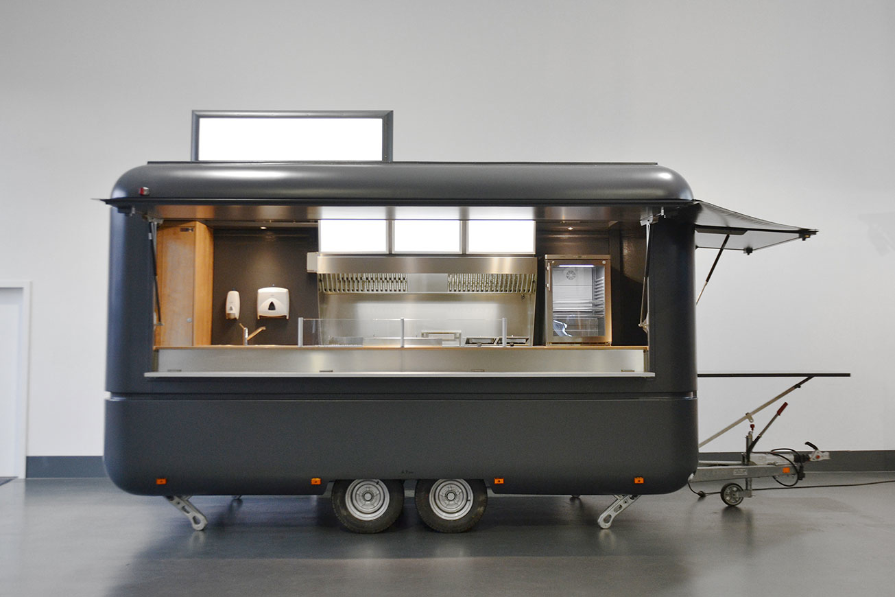 Grauer Verkaufsanhänger mit 2 Klappen, Dachdisplay und Tisch über Zugdeichsel.