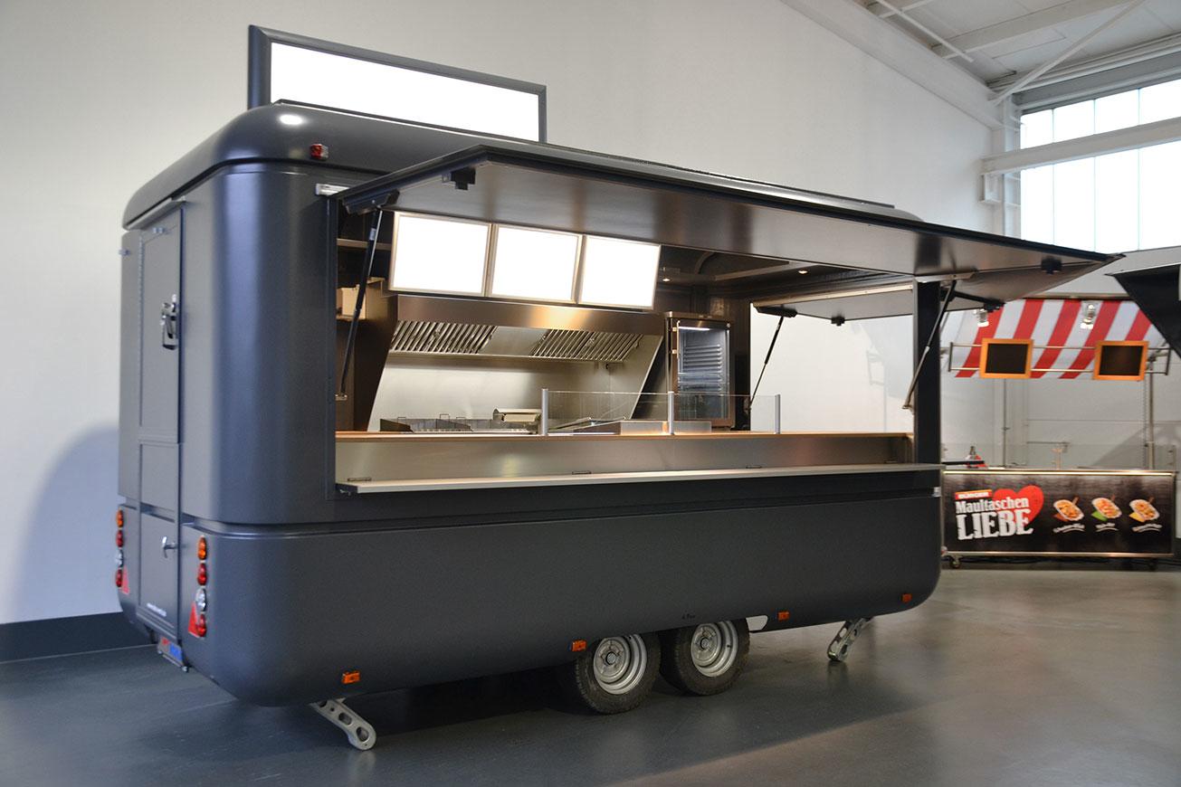 Grauer Imbisswagen mit Dachdisplay und hochwertigem Innenausbau.