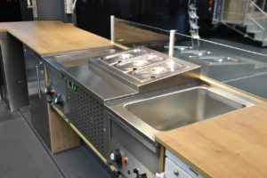 Geräte auf abgesenkter Arbeitsplatte an der Ausgabeseite des Imbissanhängers.