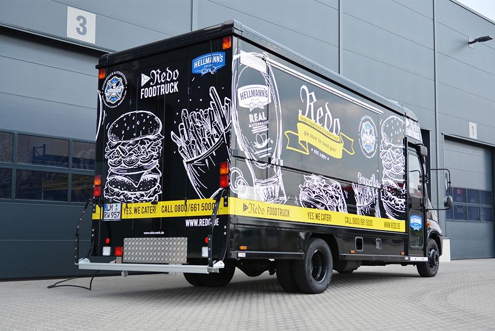 Schwarzer Food Truck mit weißen Design-Elementen.