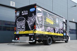 Schwarzer Food Truck mit aufwendiger Fahrzeugbeschriftung.
