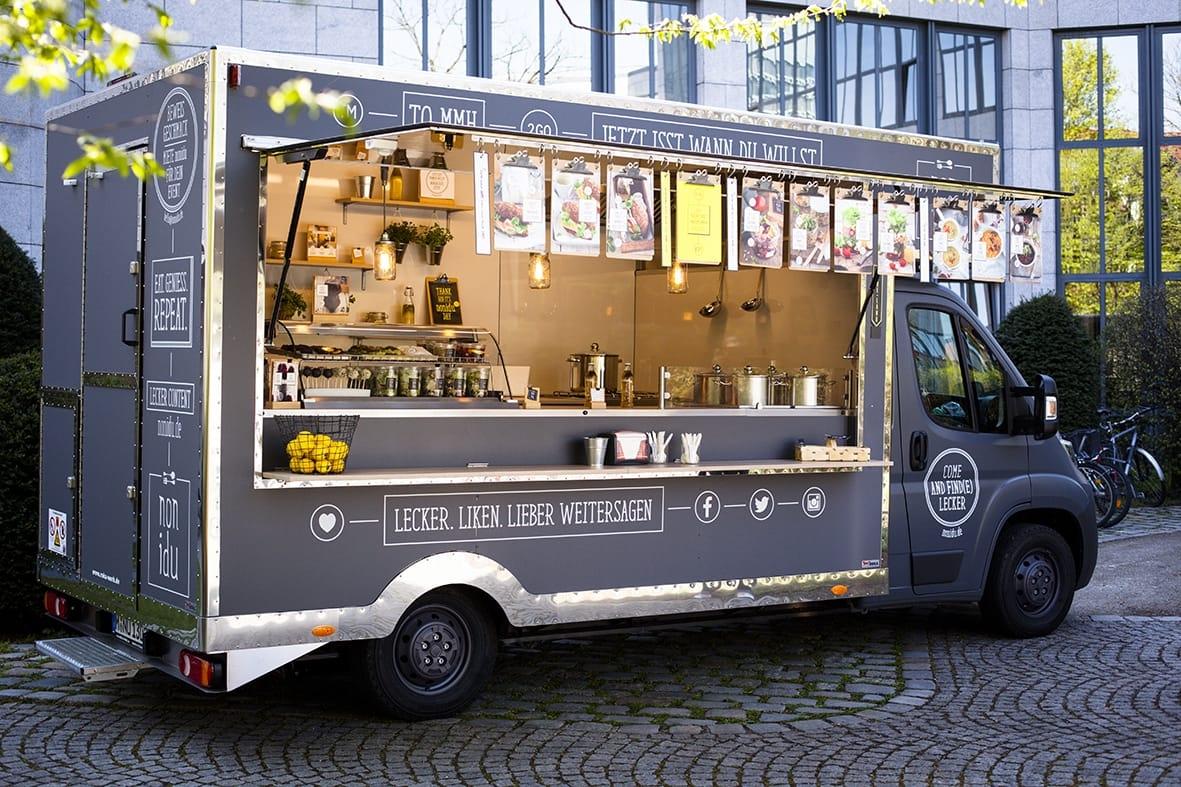 Grauer Food Truck mit Edelstahlkanten und großer Klappe.